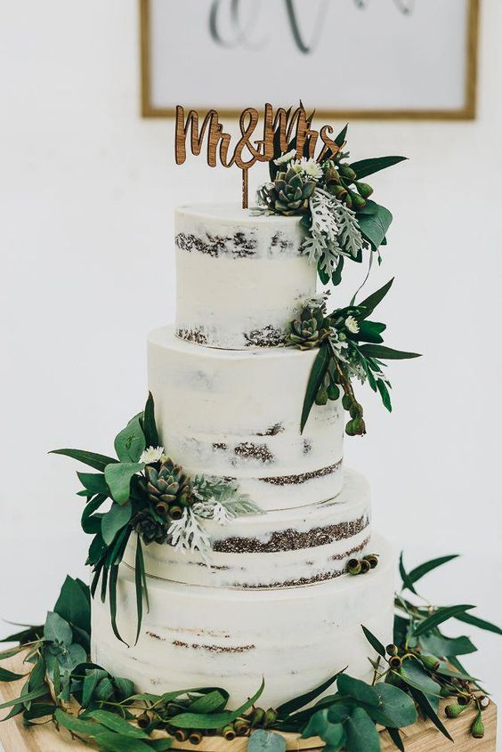 a naked wedding cake with greenery, succulents, berries, pale greenery, a wooden topper for a rustic wedding
