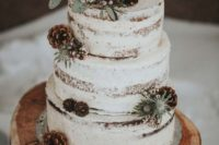 a naked wedding cake with thistles, pinecones, berries, wood slice toppers for a cozy winter wedding