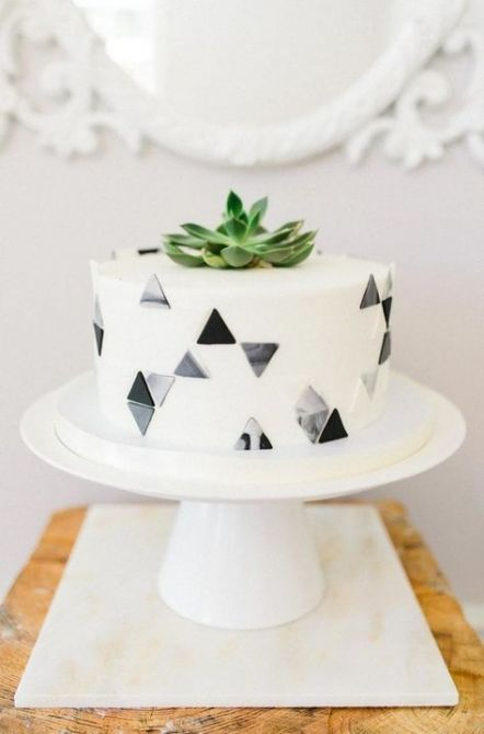 a one tier wedding cake decorated with grey and black and marbleized triangles and a succulent on top