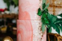 a pink marbleized wedding cake decorated with tropical leaves and gold leaf for a bright and fun tropical wedding