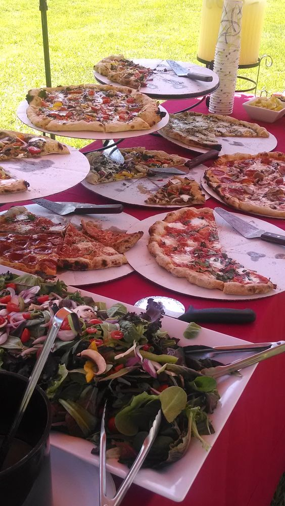 a pizza buffet done with lots of pizzas on cardboard and a large salad bowl with tongs