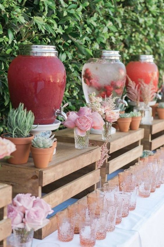 a pretty and creative drink bar with crates as stands, potted greenery and succulents, blooms, pink glasses is a very stylish idea