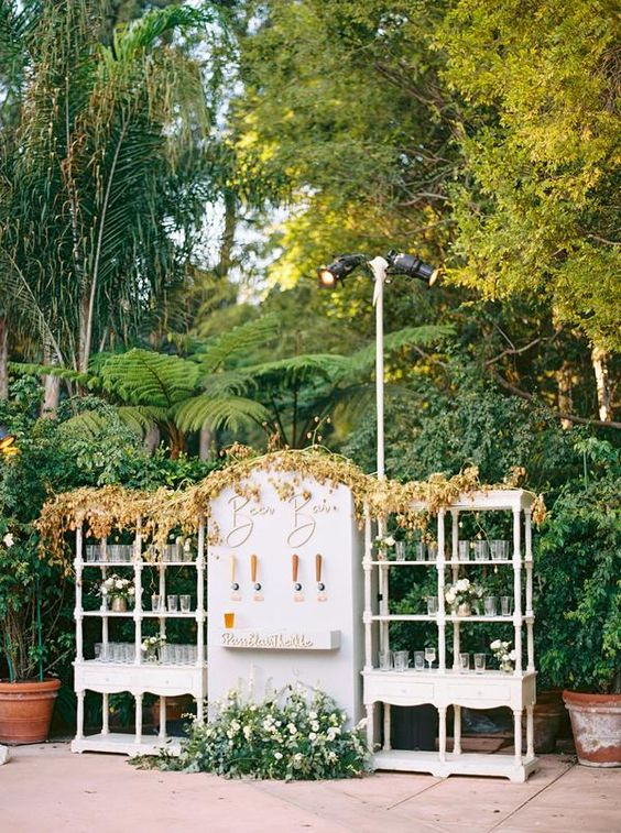 a refined and chic wedding drink bar of open shelving units and a stand with various kinds of beer, with greenery and blooms and a bold fall leaf garland