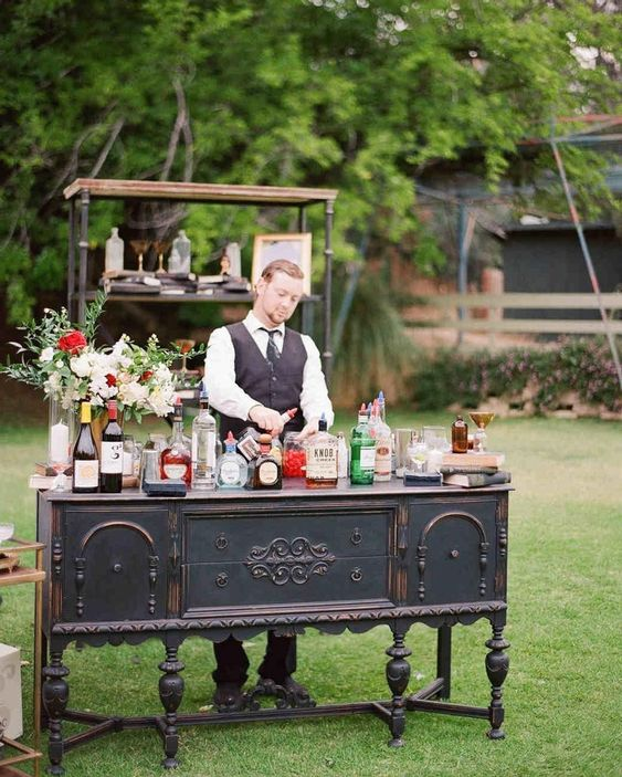 a refined vintage bar of a black buffet, an open shelving unit, blooms and lots of drinks is a very cool and sophisticated idea for your wedding