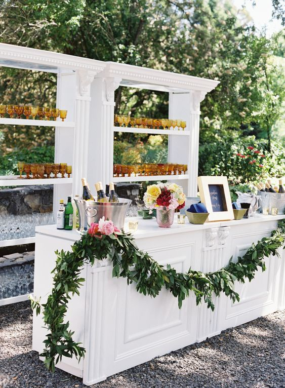 a refined wedding drink bar of a stand and a large open shelving unit, a greenery garland and lots of glasses and bright blooms in a vase is amazing