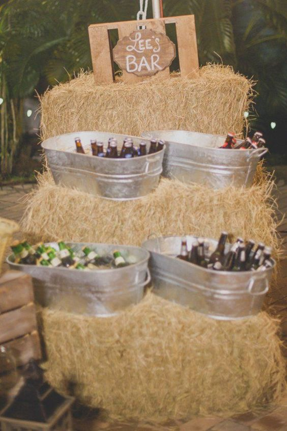 a relaxed rustic wedding drink bar composed of hay, with bathtubs, with a wooden sign is a lovely idea for a rustic wedding