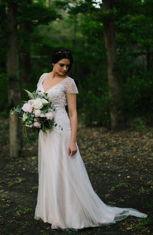 a romantic A-line wedding dress with an embellished bodice, cap sleeves and a pleated skirt plus a train