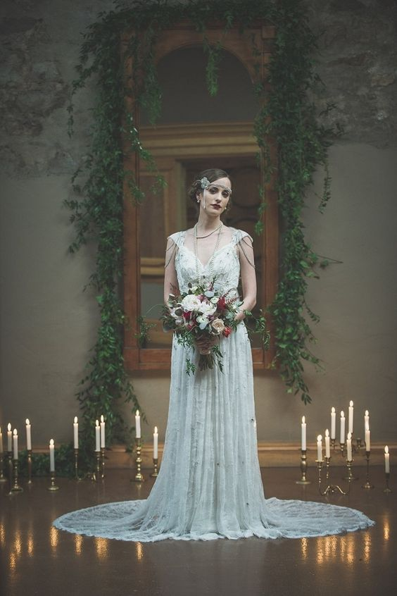 a romantic Great Gatsby wedding dress with embellishments, cap sleeves and chains on the shoulders plus a train