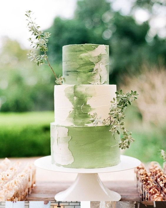a romantic green and white brushstroke wedding cake with greenery for a bright spring wedding