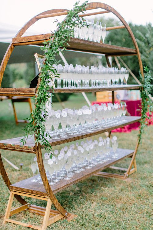 a round and open shelving unit decorated with greenery is a lovely idea for a modern rustic wedding and looks very cool