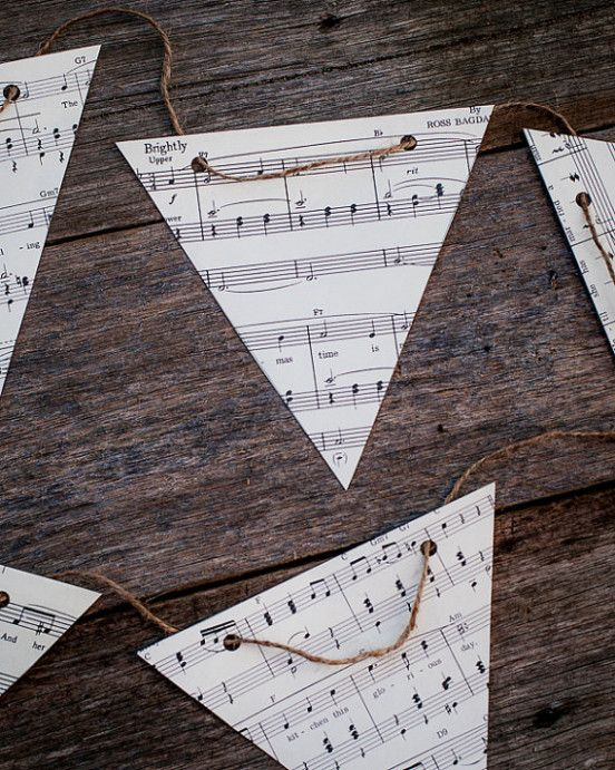 a rustic banner made of note paper triangles on twine is a simple and cool idea for a music-inspired wedding