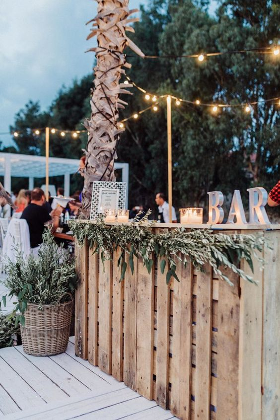 a rustic wedding bar decorated with a greenery garland, with lights and a BAR sign on the bar is a very cool and simple idea