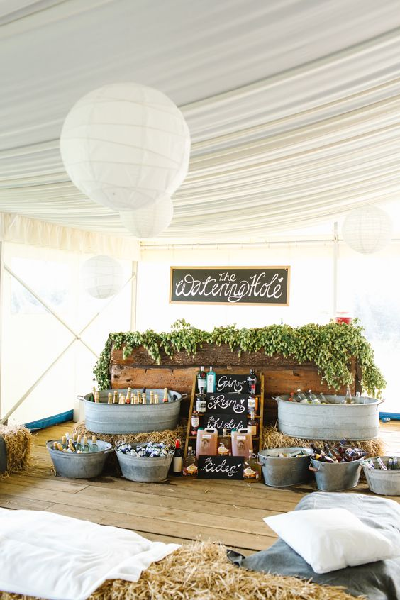 a rustic wedding bar of bathtubs with bottles, hay, potted greenery and a chalkboard sign over it is a very cool and fresh idea