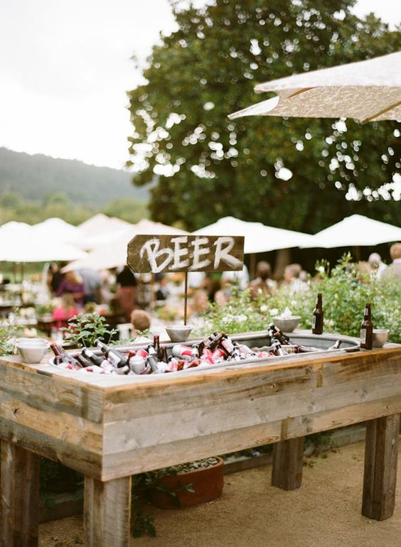 a rustic wedding bar of reclaimed wood, with greenery around, with ice and lots of bottles inside is a very cool and creative idea
