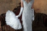 a sheath fully embellished fringe silver wedding dress with cap sleeves, a V-neckline, tall gloves and an embellished headpiece