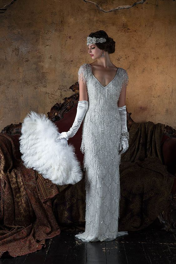 a sheath fully embellished fringe silver wedding dress with cap sleeves, a V neckline, tall gloves and an embellished headpiece