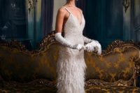 a sheath fully embellished wedding dress with a feather skirt with a train, tall gloves and a train