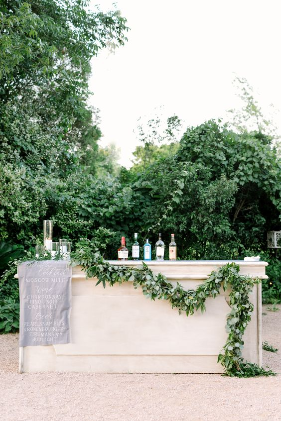 a simple and cool wedding drink bar of a white bar stand, with a greenery garland, a grey fabric menu is a lovely idea