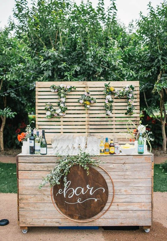 a stylish and rustic wedding drink bar of wooden planks, with greenery and bloom monograms and a greenery arrangement is a veyr chic and cool idea