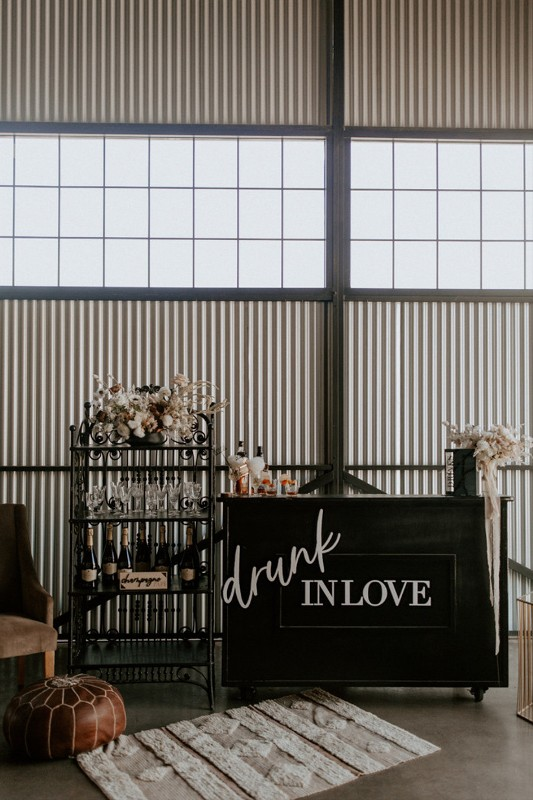 a stylish modern wedding bar of a black drink stand, a vintage metal shelving unit with neutral blooms is a lovely idea to rock