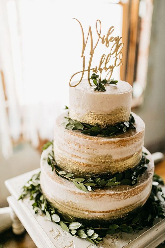 a stylish naked wedding cake with gold leaf, greenery and an elegant topper for a modern wedding
