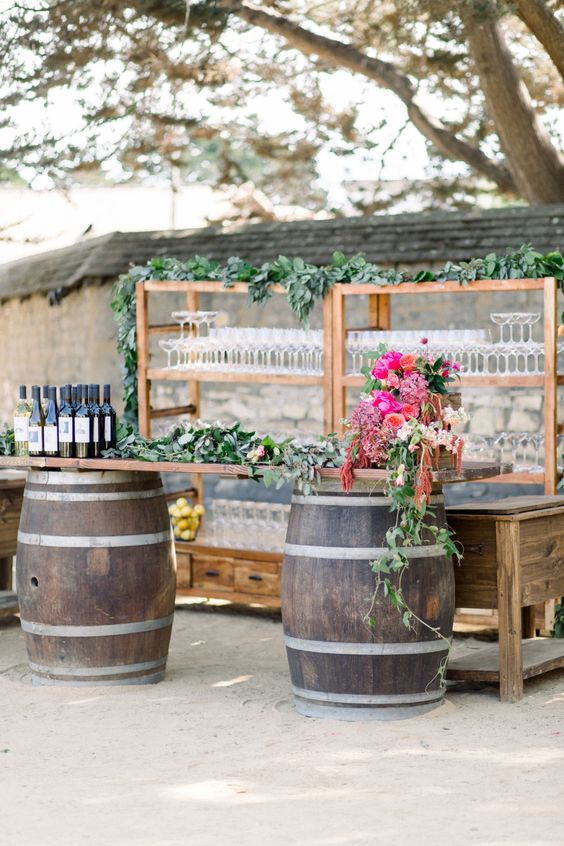 a stylish rustic wedding bar of barrels with a tabletop, bold blooms and greenery, wooden open shelves and a table is cool