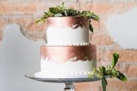 a stylish white and copper brushstroke wedding cake with greenery for a fresher look will fit a modern wedding
