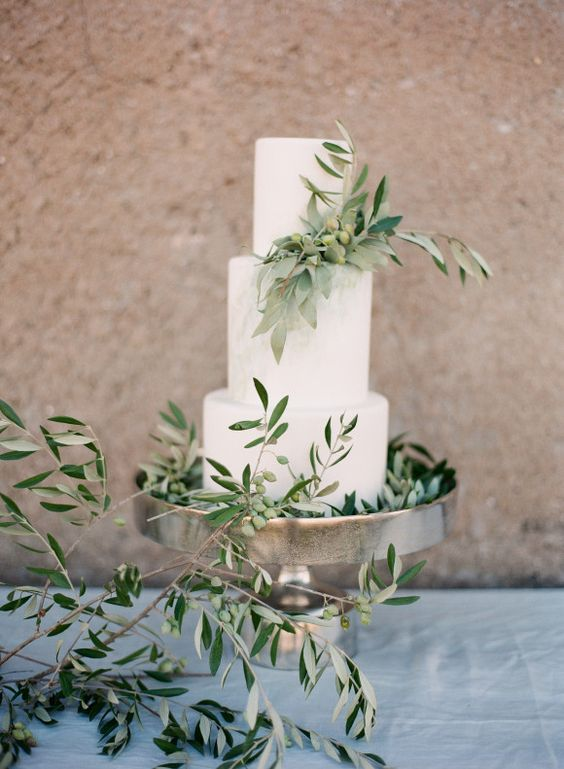 a stylish white wedding cake with olive greenery and olives for a Tuscany or Italian wedding