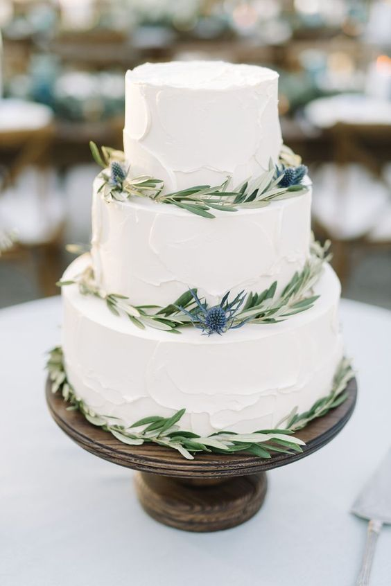 a textural white wedding cake with olive greenery and thistles for a rustic wedding