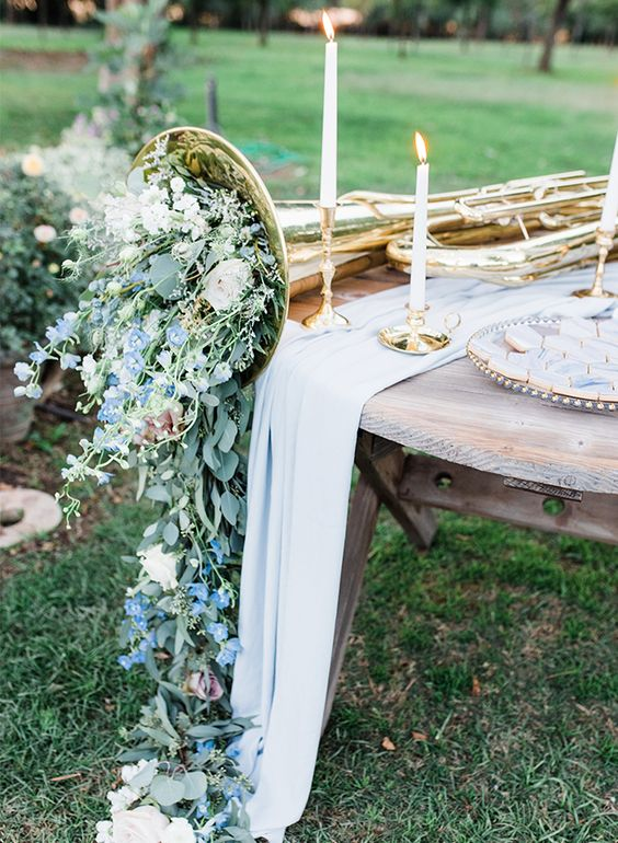 a vintage musical instrument filled with pastel blooms and greenery and some candles are amazing to make up a centerpiece