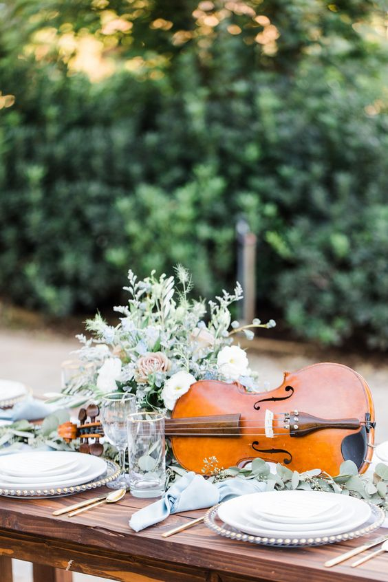 a violin dressed up with greenery and blooms will be an amazing and refined wedding centerpiece