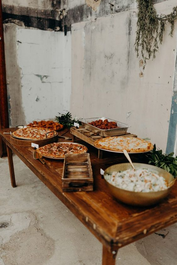 a vintage rustic pizza bar with lots of pizzas on stands and with marks plus greenery and salad in a bowl