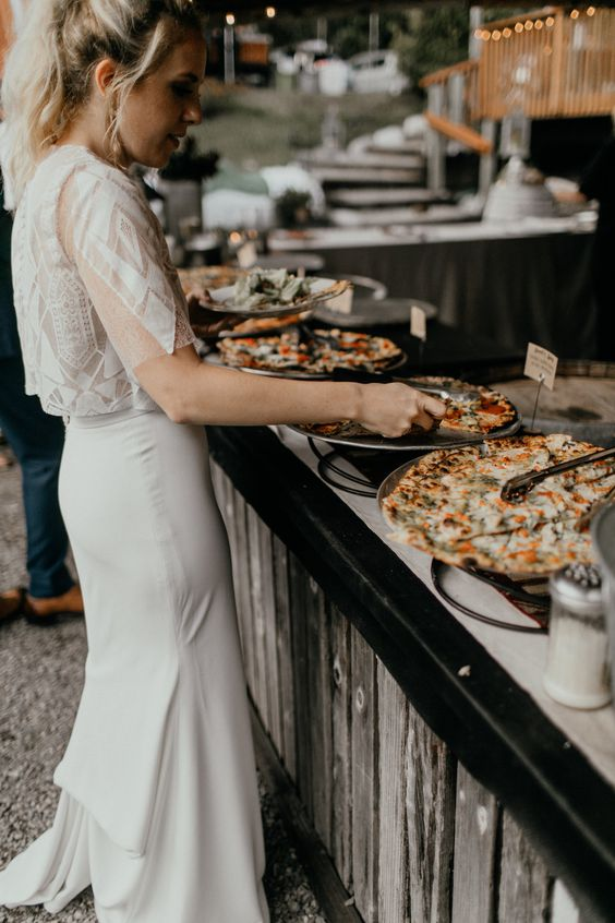 a wedding pizza bar with wire pizza stands, marks on each pizza and soem condiments