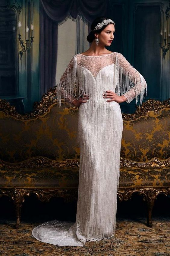 a white long fringe sheath wedding dress with an illusion neckline and sleeves and a beaded bodice plus an embellished headpiece
