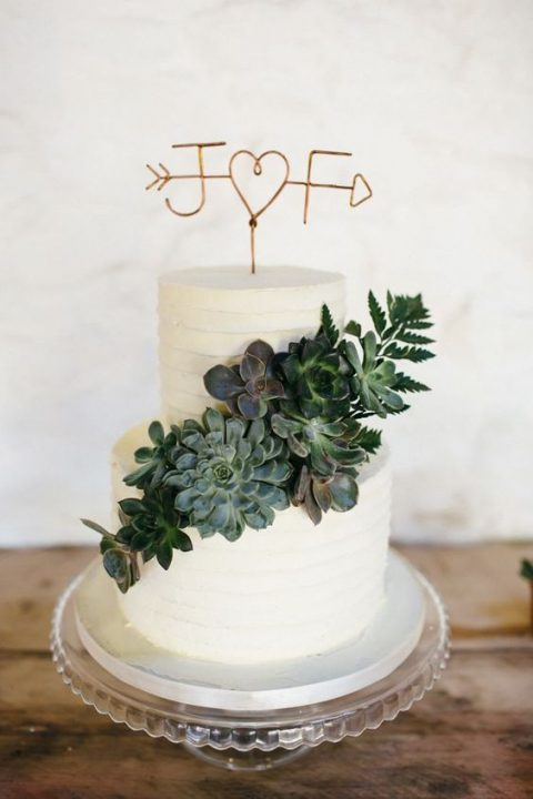 a white textural buttercream wedding cake with a topper and a fresh succulent decoration