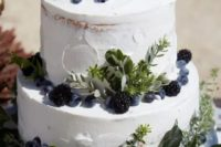 a white textural wedding cake decorated with greenery, blackberries and blueberires will fit many weddings