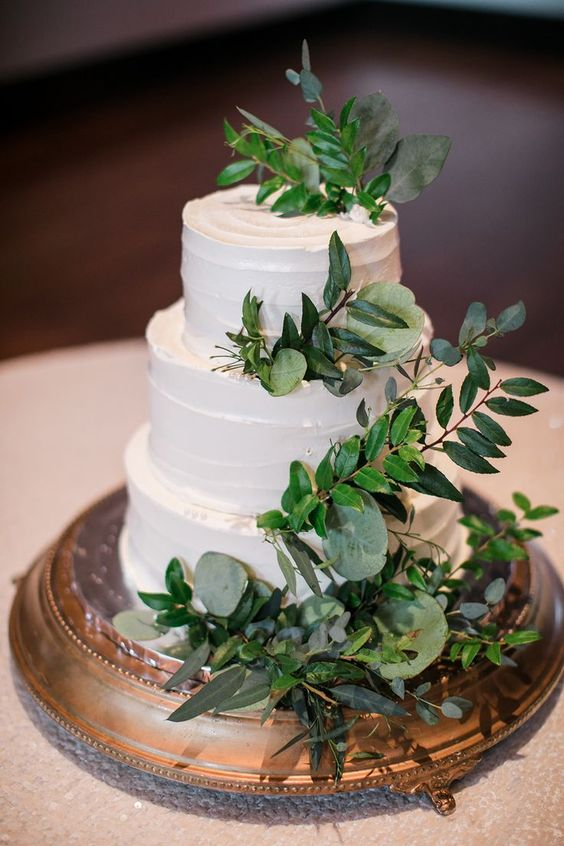 a white textural wedding cake with lush greenery and leaves for a rustic or woodland wedding