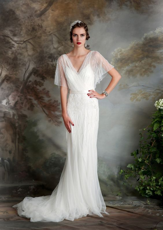 an airy and flowing wedding dress with a deep V neckline, flowy short sleeves, some matching beading