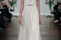 an art deco wedding dress with lace cap sleeves, a deep V-neckline with lace detailing and an embellished belt