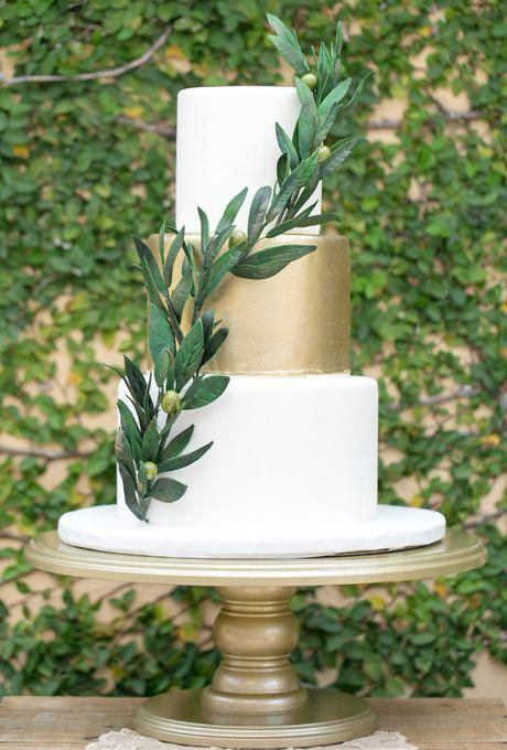 an elegant white and gold wedidng cake with an olive branch for a stylish Italian wedding