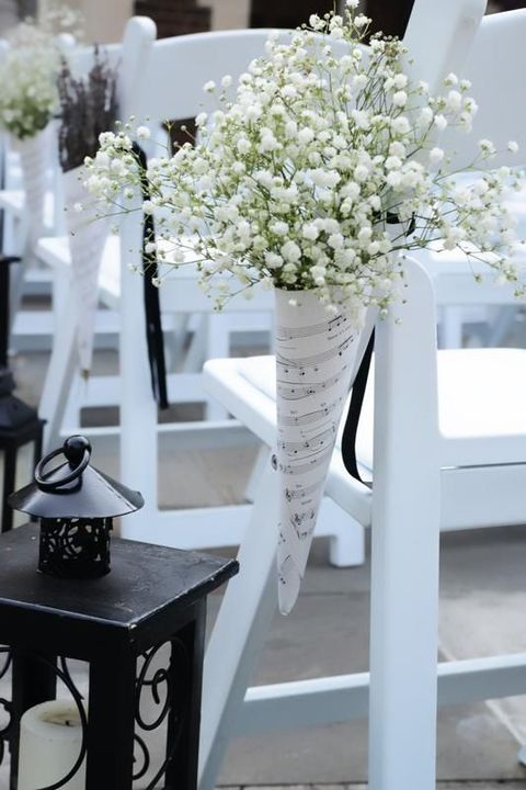 cones of note paper with baby's breath are great to decorate the chairs of the aisle
