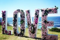 giant pink floral love letters as a wedding ceremony backdrop