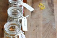 honey in small jars with tags is a cool idea for a rustic or summer wedding or rehearsal dinner