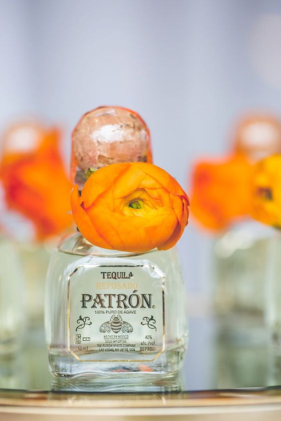 mini tequila bottles decorated with bright orange blooms are great for Mexican wedding