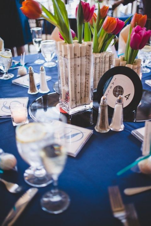 wedding centerpieces of bright tulips inserted into note paper rolls that are put into clear vases