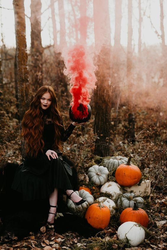 a Halloween bride rocking a black pumpkin with a red smoke bomb looks jaw-dropping and absolutely amazing