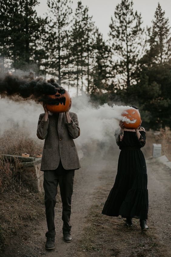 a Halloween couple rcoking Jack-o-lanterns with whiet and black smoke bombs is a very creative idea