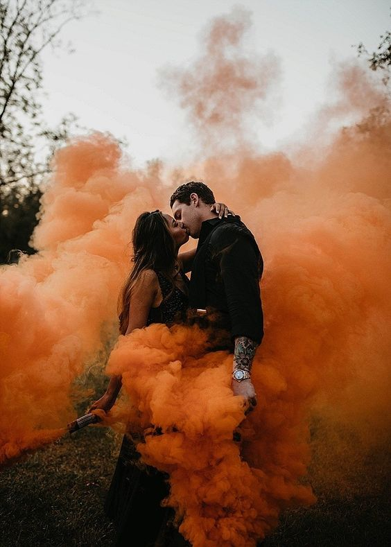 a Halloween wedding couple rocking black attire and rust-colored smoke bombs to cover themselves with bold fall shades