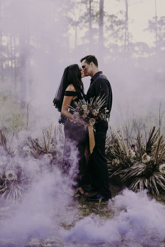 a Halloween wedding portrait at the altar and with purple smoke around for a witchy wedding