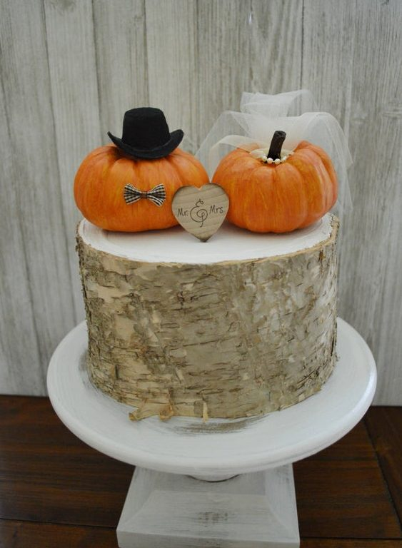 a bark wedding cake topped with faux pumpkins showing the bride and the groom and a wood slice heart is amazing